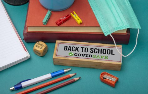 Text of back school, covid safe on table sign with surgical mask and books.
